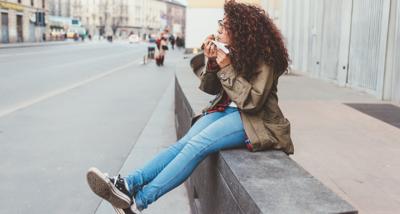 girl sits on sidewalk eating